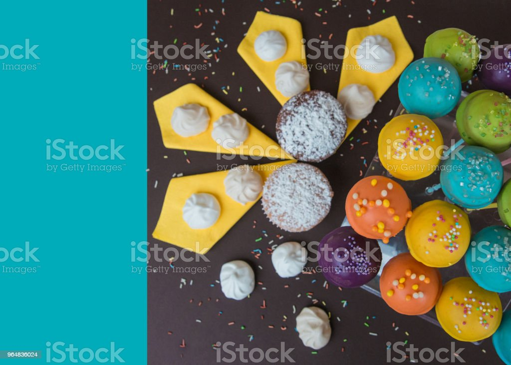 Top view of cake pops on a dark brown background with bright blue copy space royalty-free stock photo