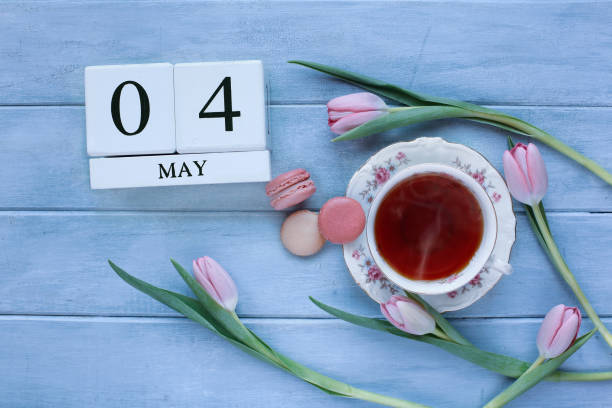 Top view of calendar blocks May 4th for National Teacher Appreciation Day with macarons Top view of calendar blocks May 4th for National Teacher Appreciation Day with macarons, hot tea, and pink tulips over a blue rustic table.. teacher appreciation week stock pictures, royalty-free photos & images
