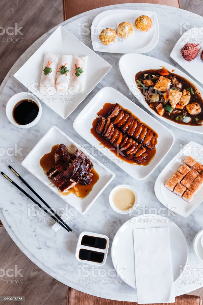 Top view of Cantonese meal including BBQ Pork, Roasted Duck, Fresh Shrimp Spring Rolls, Deep fried snapper fillets with XO Sauce and sweets on marble top round table. stock photo