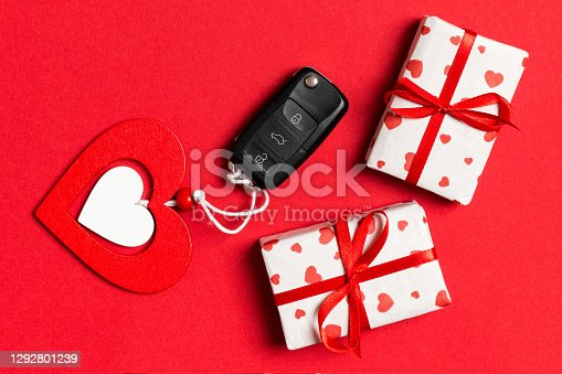 Top view of car key, gift boxes and toy heart on colorful background. Saint Valentine's Day concept with copy space.