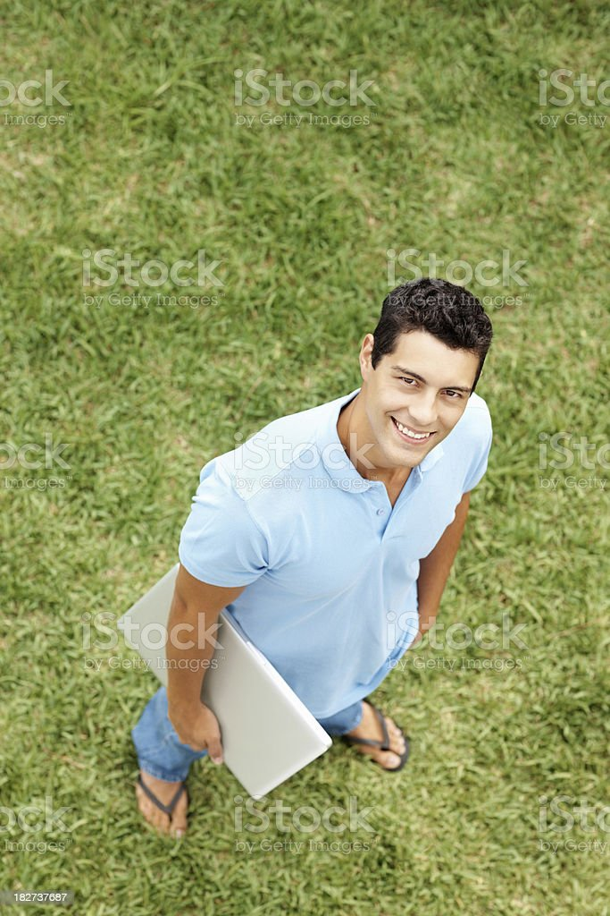 Top view of casual guy holding a laptop outdoors royalty-free stock photo