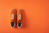 Top view of casual orange suede sneakers on orange background with copy space