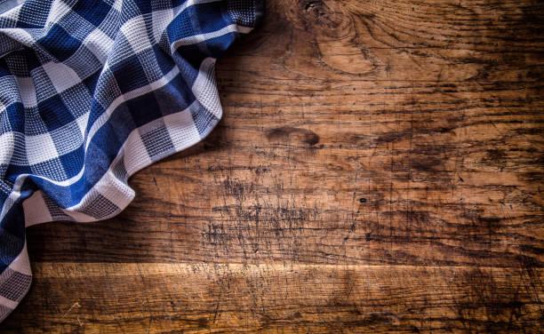 top view of checkered tablecloth  on empty wooden table - klapprahmen stock-fotos und bilder