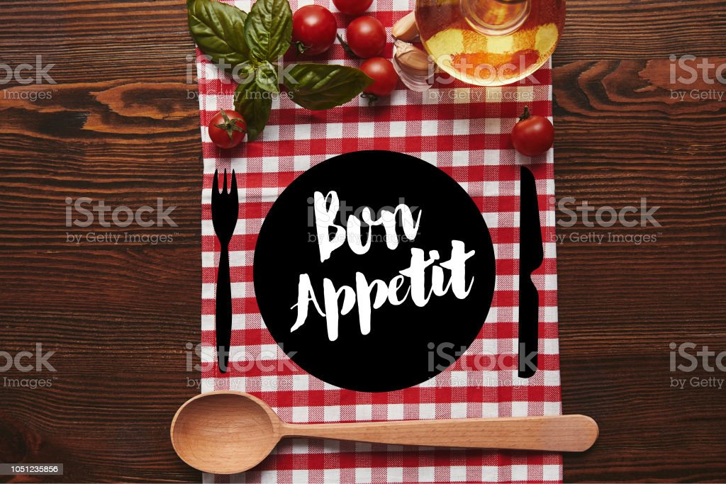 top view of checkered tablecloth, wooden spoon and fresh basil with tomatoes and oil on wooden surface with 'bon appetit' lettering stock photo