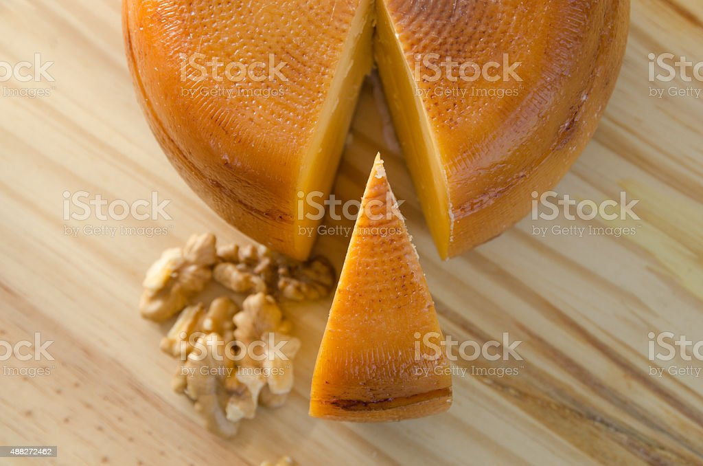Top view of cheese wheel and slice with nuts stock photo