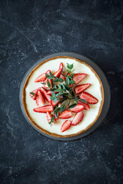 top-ansicht von käsekuchen mit erdbeeren verziert - obst käsekuchen stock-fotos und bilder