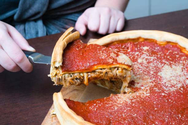 Top-Ansicht von Chicago Pizza. Frau Hände schneiden Chicago Stil tief Gericht italienischen Käse Pizza mit Tomatensauce und Rindfleisch treffen innen – Foto