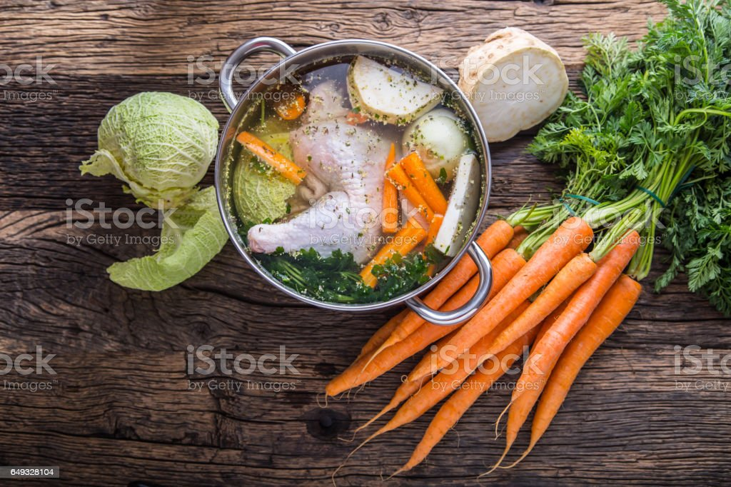 Top view of chicken soup -  broth on wooden table with vegetable stock photo