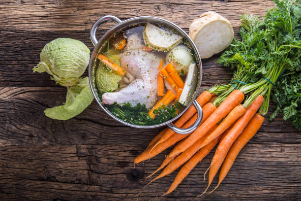 Top view of chicken soup -  broth on wooden table with vegetable - Photo