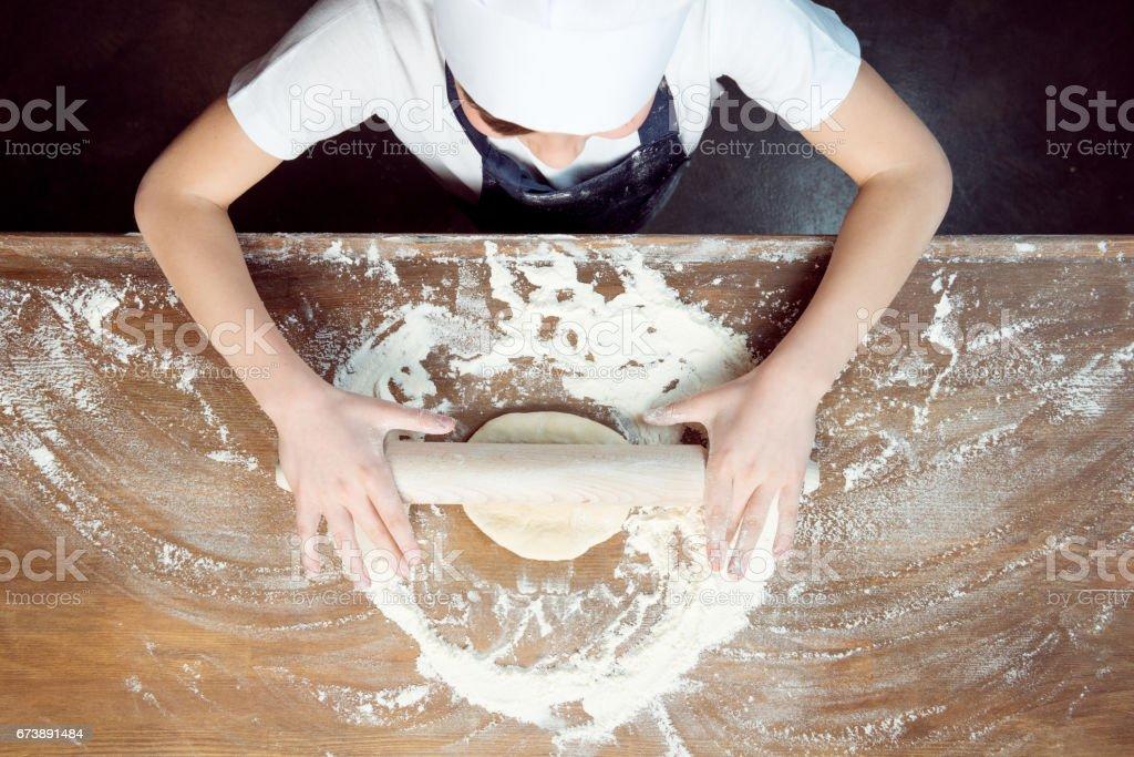 vue de dessus d'enfant faire la pâte à pizza sur la table en bois photo libre de droits