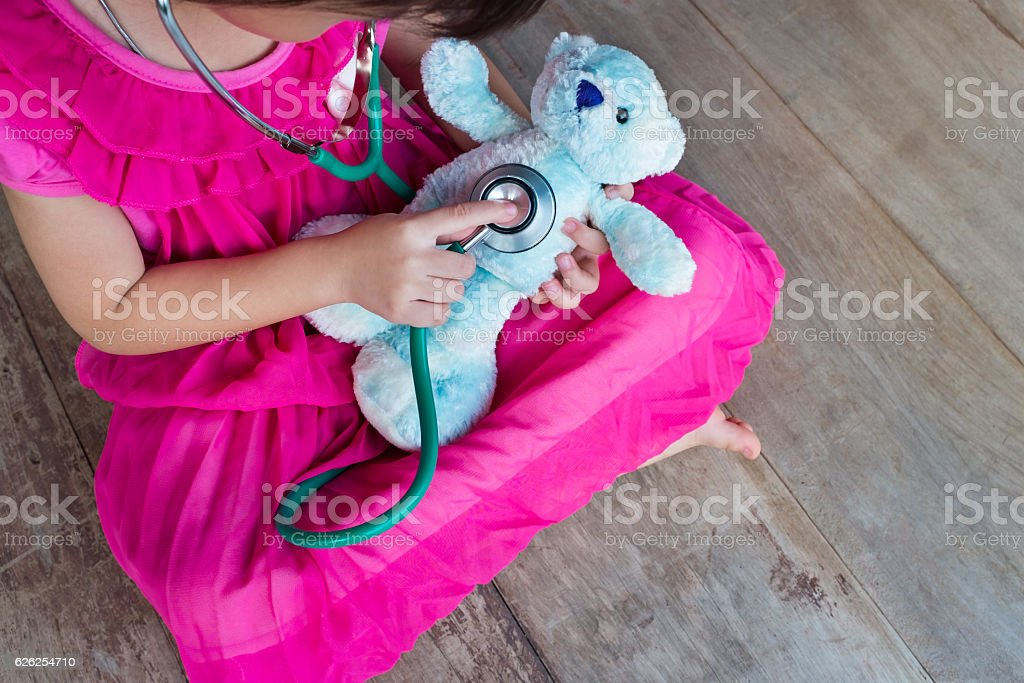 Top view of child playing doctor with plush toy bear. stock photo