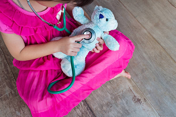 top view of child playing doctor with plush toy bear. - doktorspiele stock-fotos und bilder