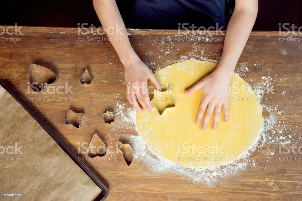top view of child with raw shaped cookies and cookie cutters on wooden table stock photo