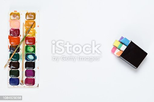 949860388istockphoto Top view of children paints, brushes and crayons, flat lay. Back to school concept. 1084529258