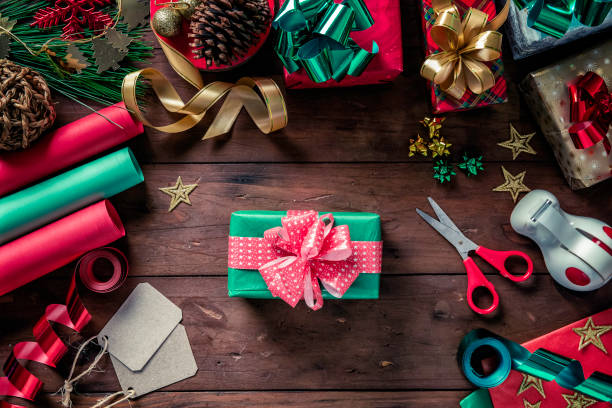 Top view of Christmas wrapping accessories and finished gift box. Christmas themes. Top view of Christmas wrapping accessories and finished gift box navidad stock pictures, royalty-free photos & images