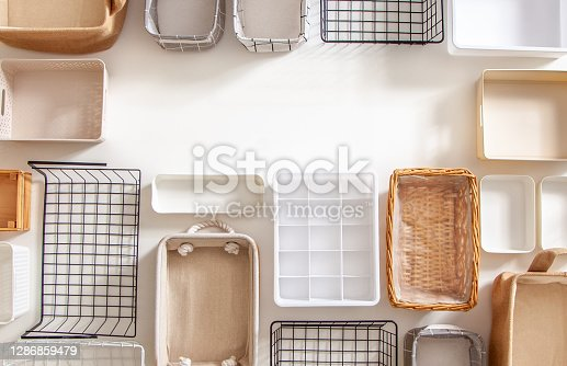 Top view of empty closet organization boxes and steel wire baskets in different shape placed on white marble table with copy space. Marie Kondo hikidashi boxes for tidying clothes and drawer storage