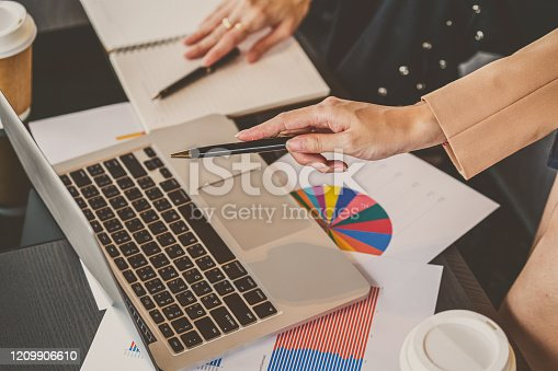950986656 istock photo Top view of closeup asian businesswomen holding and pen pointing to technology laptop in modern meeting room 1209906610