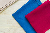 Top view of cloth napkins of beige, blue and burgundy colors on rustic white background.