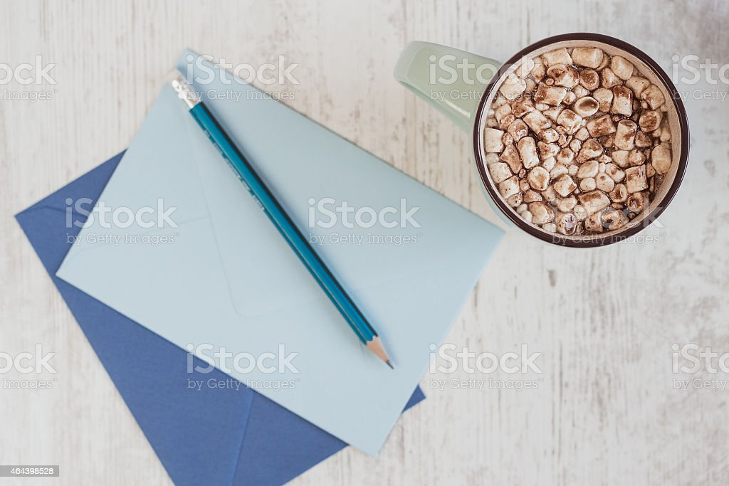 Top view of cocoa with marshmallow and blue envelopes stock photo