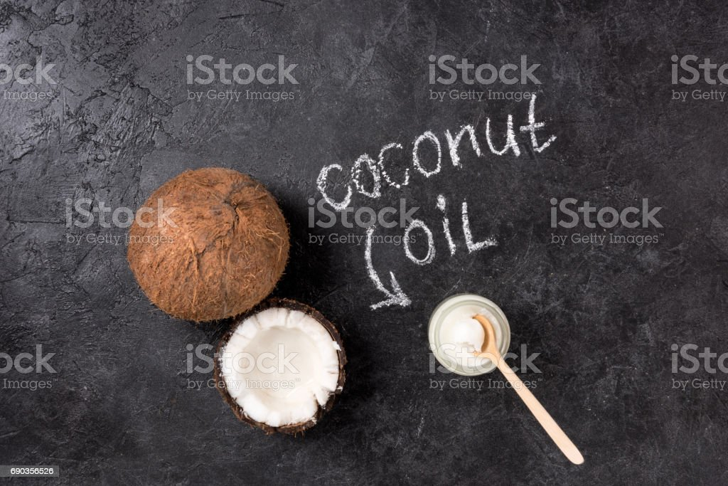 Top view of coconut oil in glass jar with spoon and cracked coconut on black stock photo