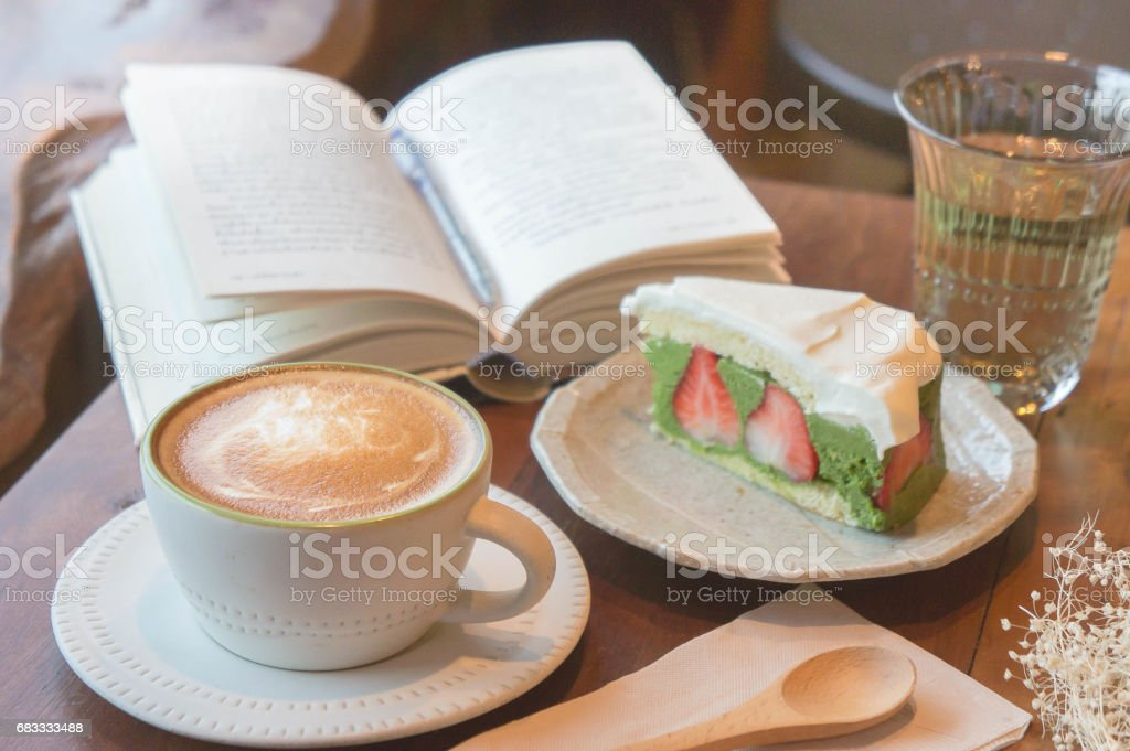 Top view of coffee cup and green tea cake , book , on table in coffee shop relax time royalty-free stock photo