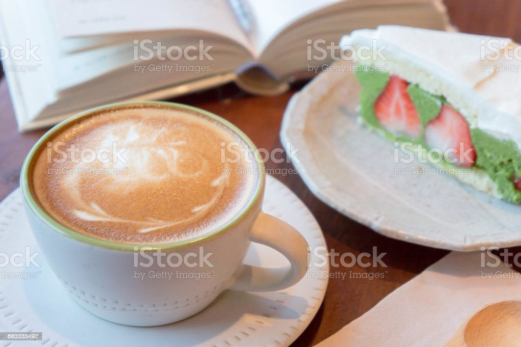 Top view of coffee cup and green tea cake, book , on table in coffee shop relax time royalty-free stock photo