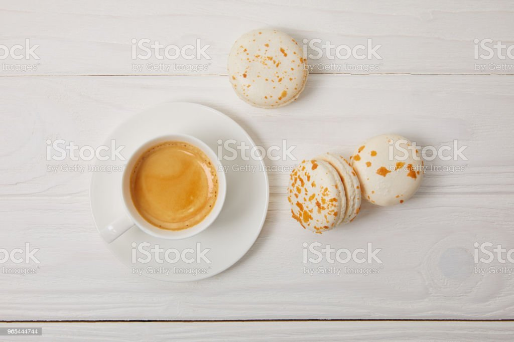 top view of coffee cup and three macarons on white wooden table royalty-free stock photo