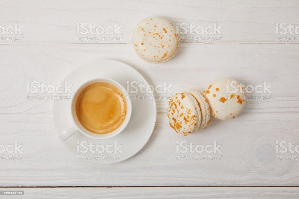 咖啡杯和三馬卡龍在白色木桌上的最高視圖 - 免版稅俯視圖庫照片