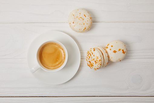 咖啡杯和三馬卡龍在白色木桌上的最高視圖 照片檔及更多 俯視 照片