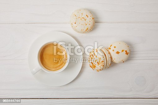 Top View Of Coffee Cup And Three Macarons On White Wooden Table Stock Photo & More Pictures of Backdrop - Artificial Scene