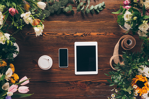 top view of coffee in paper cup, smartphone and tablet on table with flowers