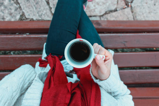 top view of coffee mug in womans hand sitting on the bench stock photo