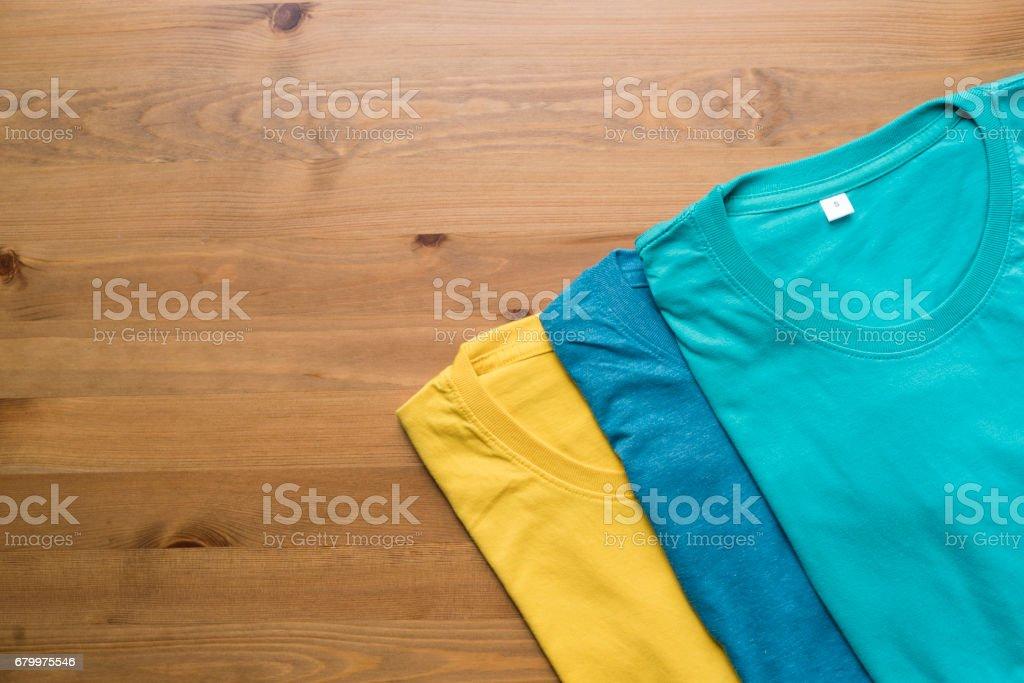 Draufsicht der Farbe T-Shirt auf schwarzem Hintergrund – Foto