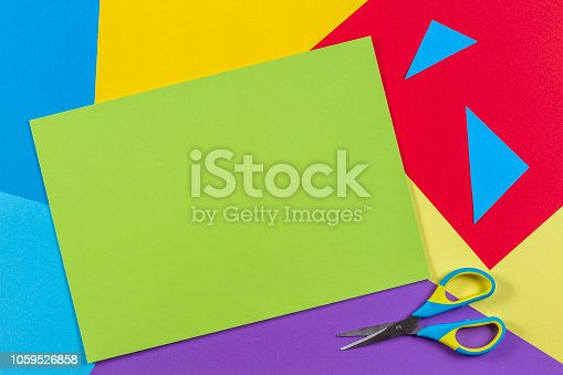 istock Top view of colored paper with colorful scissors. Kids art and craft paper applique background 1059526858