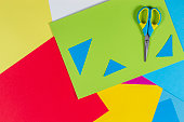 Top view of colored paper with colorful scissors. Kids art and craft paper applique background