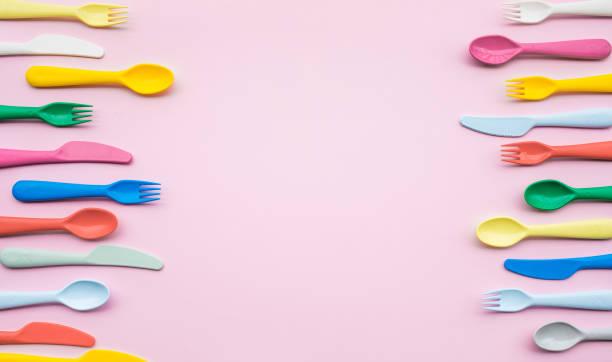 top vy av färgglada sked och gaffel element på färgtabell. flat lay - bordsskick bildbanksfoton och bilder