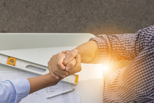 912867216 istock photo Top view of construction engineer team and business man shaking hands after meeting at construction site with blurred plan and tools background, success teamwork concept. 849926656
