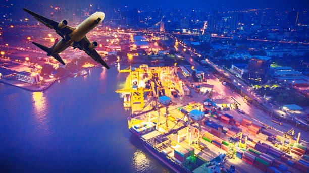 top view of container ship and aircraft in export and import business and logistics. shipping cargo to harbor by crane. aerial view container cargo ship and cargo plane with working crane bridge in shipyard. logistics - drone shipyard night imagens e fotografias de stock