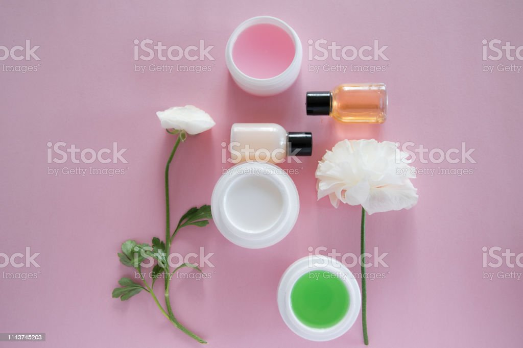 Top view of cosmetic products and delicate flowers on pink...