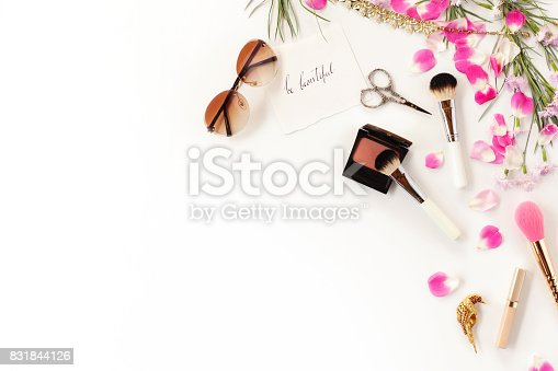 istock Top view of cosmetics and female accessories on white with pink petals. Beauty blog flat lay concept. 831844126