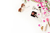 Top view of cosmetics and female accessories on white with pink petals. Beauty blog flat lay concept.