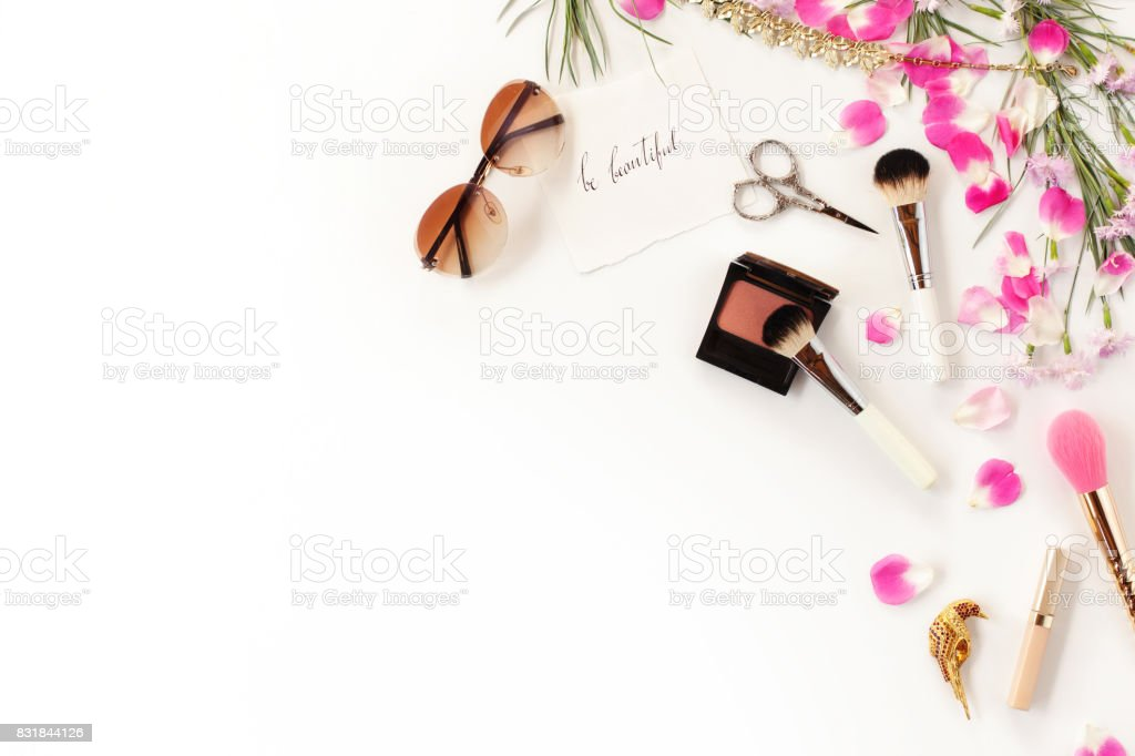 Top view of cosmetics and female accessories on white with pink petals. Beauty blog flat lay concept. stock photo