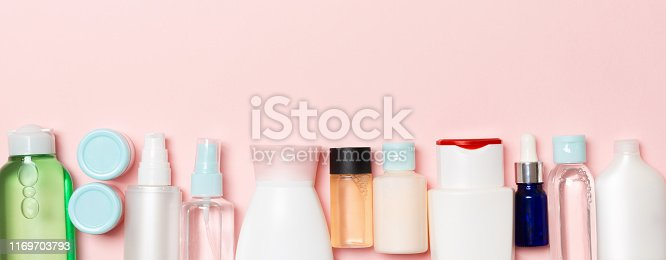 istock Top view of cosmetics bottles on pink background. Skin care concept with space for your design 1169703793