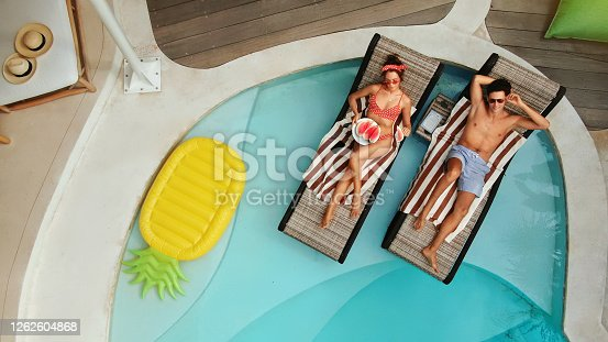 Top View Of Couple At Pool. Happy Man And Woman Enjoying Summer Vacation Or Honeymoon At Tropical Villa. Romantic Summertime On Poolside At Luxury Resort. Fashion Male And Female In Love.