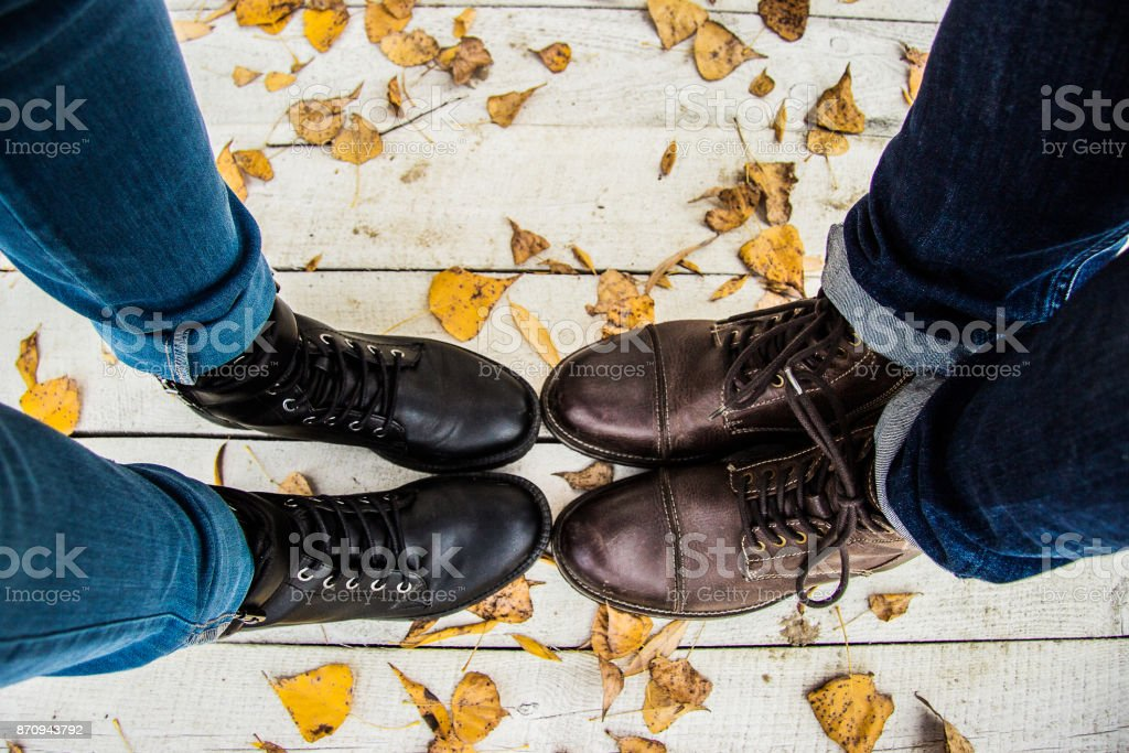 Top view of couple feet in stylish boots. stock photo