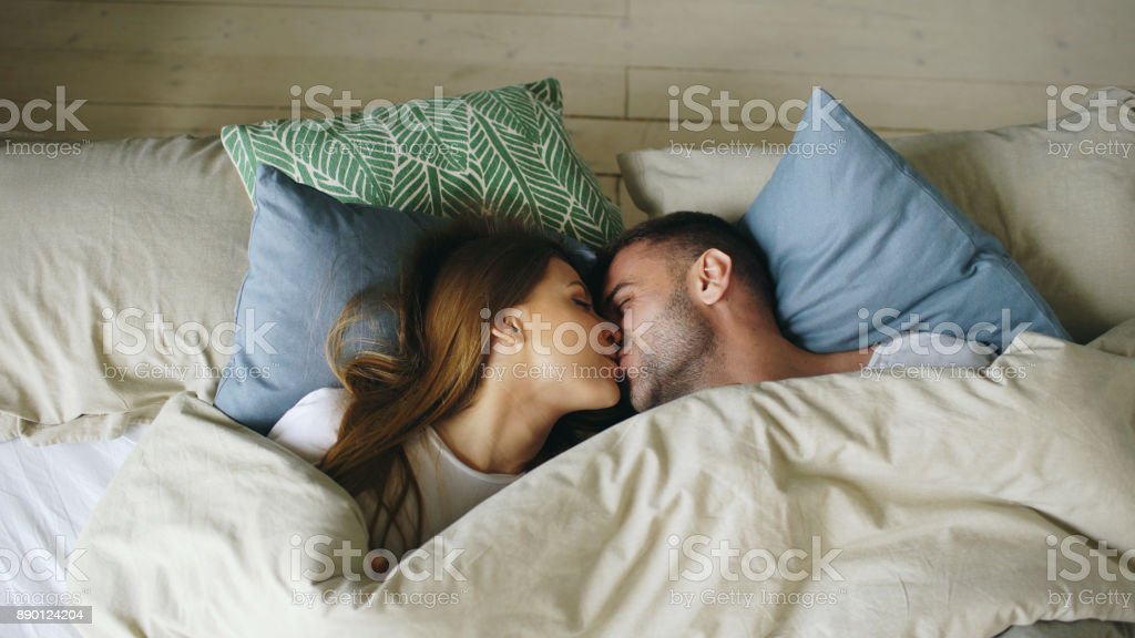 Top view of couple having fun in bed lying under blanket looking into camera and kissing at home stock photo