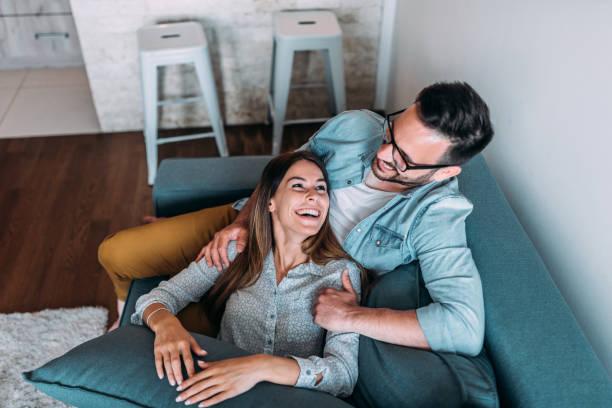top view of couple relaxing on sofa. - couple стоковые фото и изображения