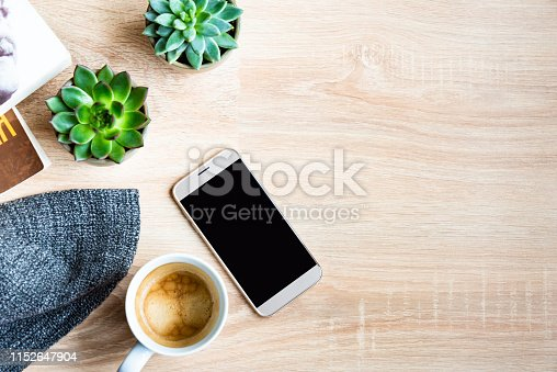 Top view of cozy home scene. Books, woolen blanket, cup of coffee and succulent plants over wooden background. Copy space, mock-up.