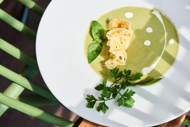 Top-Ansicht der Sahnesuppe von Zucchini, Hühnerbrühe und frischem Parmesan auf weißem Hintergrund – Foto
