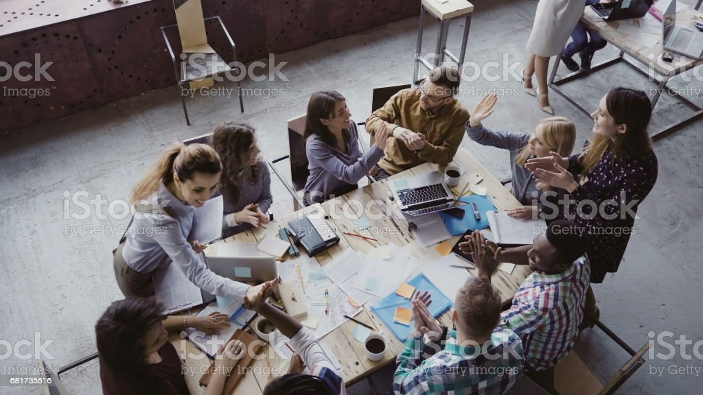 Top view of creative business team working at modern office. Colleagues talking, smiling, high five with each other stock photo